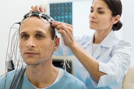 환자의 머리에 전극을 고정하는 여성 의사