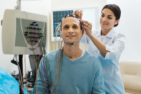 Weibliche Arzt entfernen Elektroden von Patienten Kopf Standard-Bild - 84106264