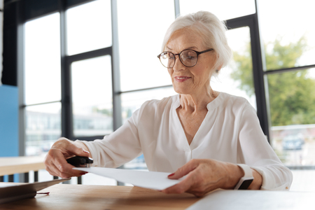 Joyful positive woman joining pages of documents