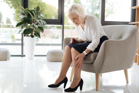 Unglückliche, fröhliche Frau, die ihre Beine ansah Standard-Bild - 83991900