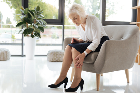 Unhappy cheerless woman looking at her legs