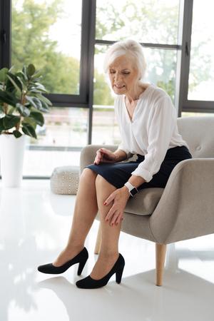 Gloomy senior woman feeling pain in her legs Stock Photo