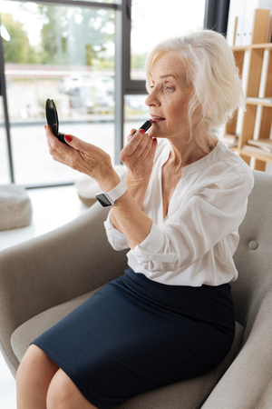 Delighted good looking woman putting on some lipstick