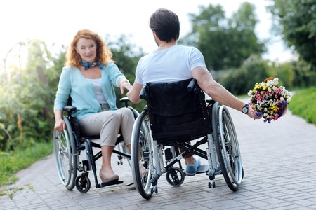 Pleasant wheelchaired man presenting flowers her wife