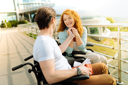 Cheerful disabled woman looking at her loving husband with love