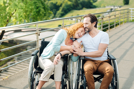 Cheerful senior woman embracing her loving wheelchaired husband Stock Photo