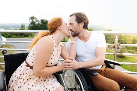 Nice wheelchaired couple kissing outdoors Stock Photo