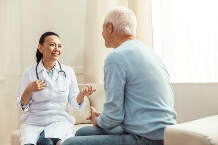Begeisterte positive Krankenschwester, die mit ihrem Patienten spricht Standard-Bild - 84776899