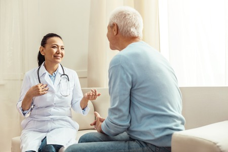Delighted positive nurse talking to her patient Stockfoto