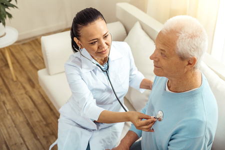 Positive delighted nurse sitting with her patient