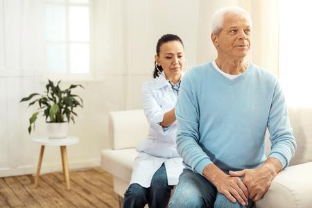 Médico serio inteligente sentado detrás de su paciente