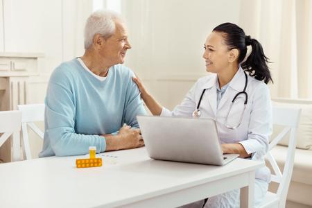 フレンドリーな思いやりのある医者患者の肩に手を置くと