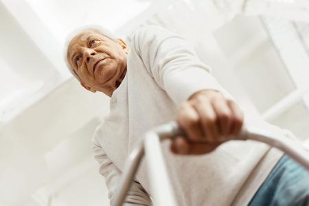 Thoughtful senior man leaning on the walking frame