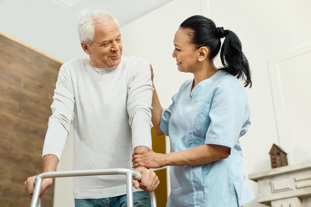 Cheerful friendly nurse helping the elderly man
