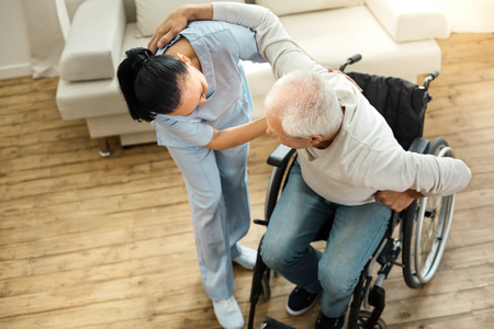 Nice elderly man using caregivers help