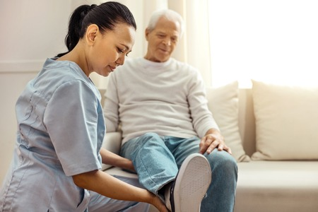 Delighted pleasant nurse looking at her patients leg