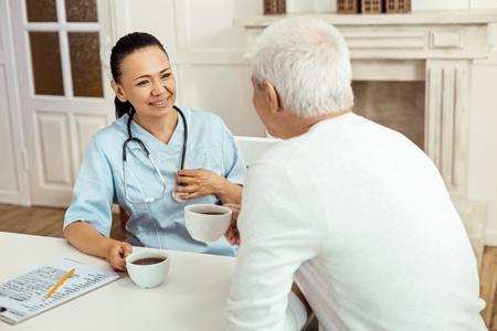 Joyful positive caregiver having tea with her patient