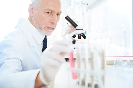 Handsome medical worker sitting in laboratory Stock Photo