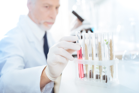 Confident lab assistant taking tube with reagent