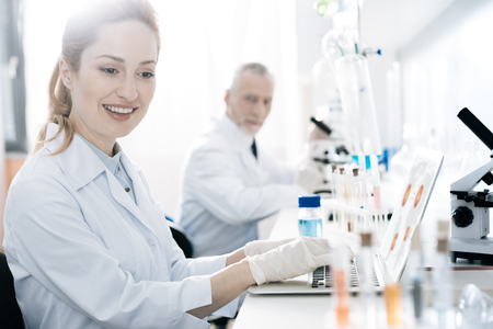 Positive delighted blonde looking at set with test tubes