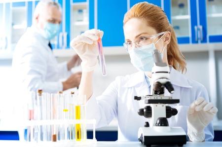 Serious researcher watching pink liquid