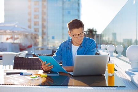 Handsome student doing homework in cafe