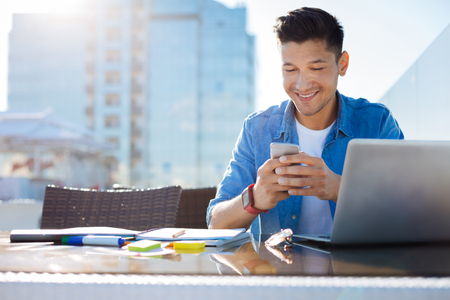 Radiant guy reading text message on smartphone Stock Photo