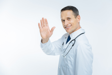 Positive minded mature doctor waving hello over background