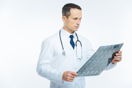Serious male physician looking at mri scan of patient head