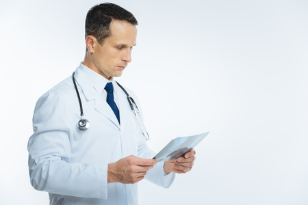 Side view on serious physician examining magnetic resonance image Stock Photo