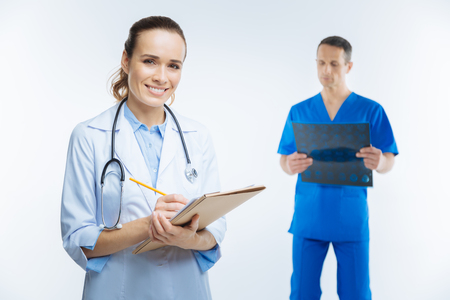 Cheerful doctor with notebook smiling into camera