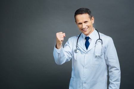 hurray: Excited male doctor gesturing while posing for camera Stock Photo
