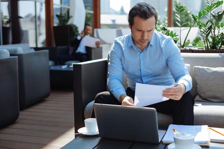 Slimme serieuze zakenman die documentatie bestudeert