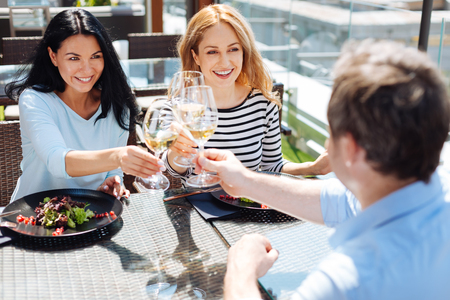 Happy delighted people cheering with wine Stock Photo