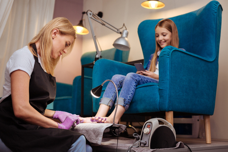 Professional manicurist doing pedicure to her teenage client Imagens