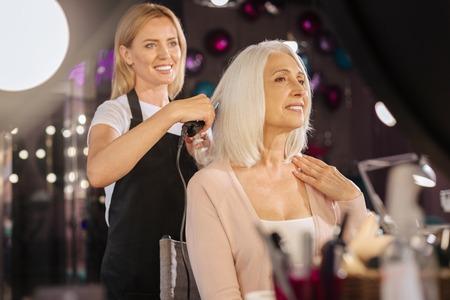 Pleasant hairdresser using straightening iron on clients hair