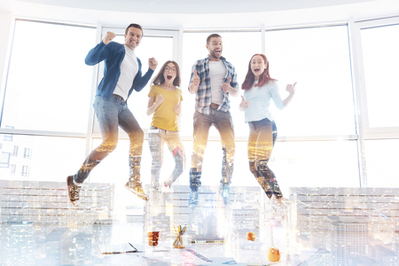 Smart cheerful students jumping together Stock Photo