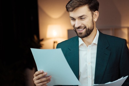 Portrait of delighted man that looking at papers Reklamní fotografie
