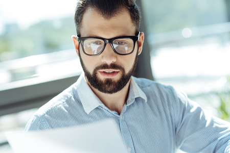 Close up of pleasant bearded man scrutinizing documents