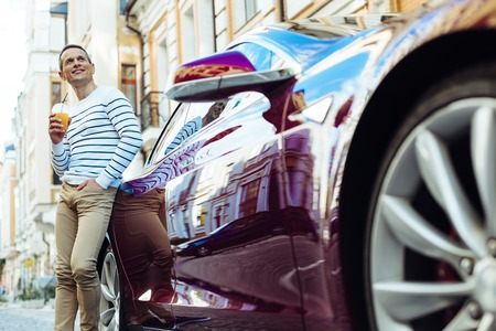 Cheerful nice man resting near his car Stock Photo