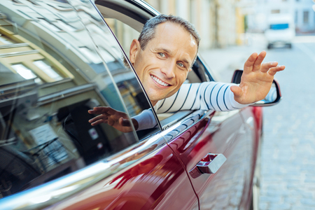 Cheerful positive man putting his hand of the car window Stock Photo