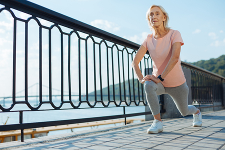Slender elderly woman doing lunges on the bridge