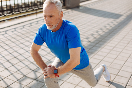 Pleasant senior man performing lunges in the street Stock Photo