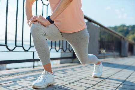 Close up of elderly woman doing lunges before jogging Stock Photo