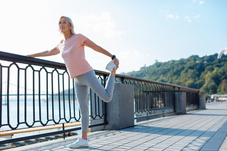 Athletic woman stretching her leg on the bridge