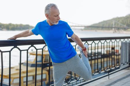 Senior man warming up before morning run