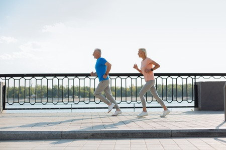 Energetic elderly couple running together in the waterfront area
