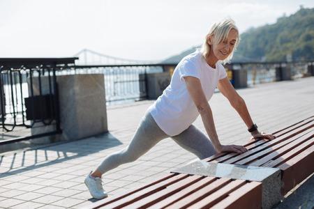 Slender senior woman stretching near bench Stock Photo