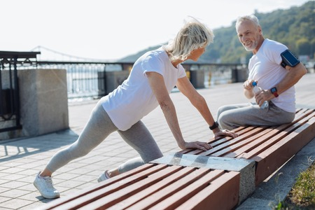 Upbeat man watching his wife do stretching exercises