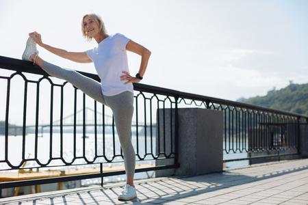 Charming senior woman stretching near bridge balustrade
